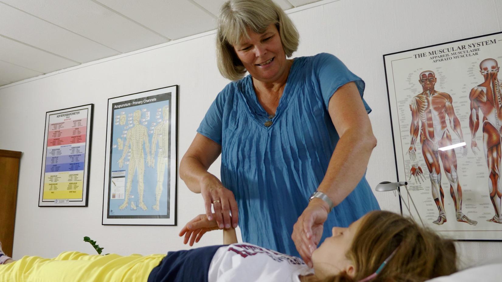 Hanne tester musklen på en pige der ligger på en briks og kigger ned mod fødderne.