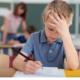 Dreng med en skoleopgave ser opgivende og modløs ud