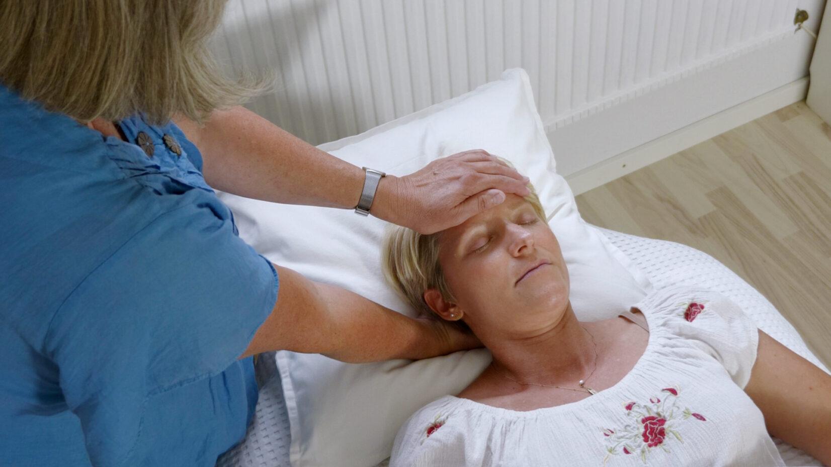 Kvinde ligger med hovedet på puden og får stressfrigørelse ved berøring af pande og baghoved