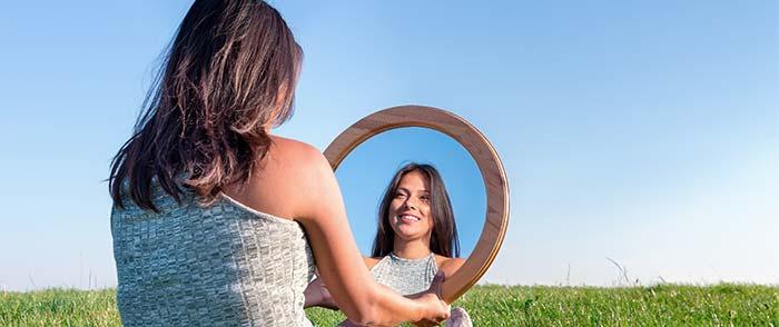 kvinde sidder på græs og kigger glad på sit eget spejlbillede