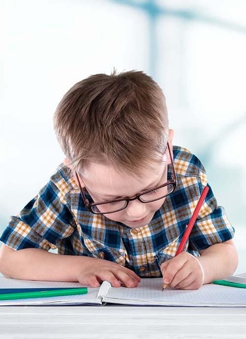 skoledreng med briller skriver ivrigt med rød blyant