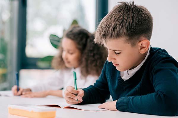 to skoleelever sidder koncentreret og skriver i deres bøger