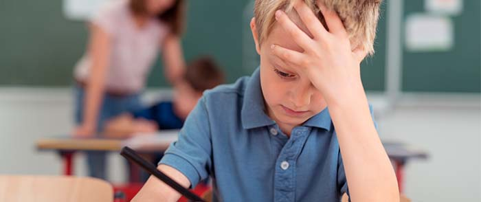 skoledreng tager sig til panden og ser frustreret ud imens han laver en skoleopgave