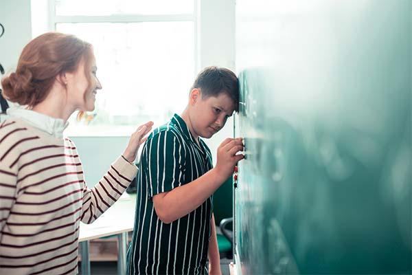 skoledreng læner sig op ad en tavle imens en kvindelig lærer opmuntrer ham