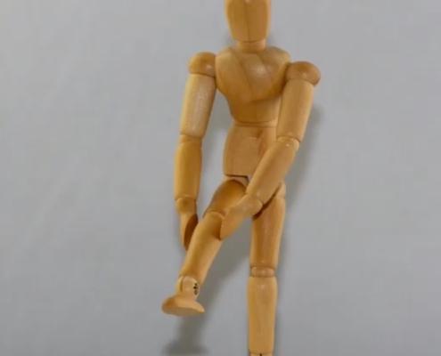 træfigur strækket det ene ben ud og holder på sit knæ